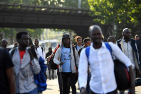 """Migrants and refugees carry their belongings during the evacuation of a makeshift camp at Porte de la Chapelle, northern Paris, on July 7, 2017, one of several camps sprouting up around the French capital..French authorities proceeded to the evacuation of more than 2,000 migrants settled in a makeshift camp in the north of Paris, a few days before the presentation of a """"migrant plan"""" by the government. / AFP PHOTO / Eric FEFERBERG"""