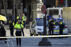 """Medical staff members and policemen stand in a cordoned off area after a van ploughed into the crowd, injuring several persons on the Rambla in Barcelona on August 17, 2017..Police in Barcelona said they were dealing with a """"terrorist attack"""" after a vehicle ploughed into a crowd of pedestrians on the city's famous Las Ramblas boulevard on August 17, 2017. Police were clearing the area after the incident, which has left a number of people injured. / AFP PHOTO / Josep LAGO"""