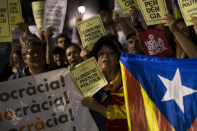 """People hold Esteladas (Pro-independence Catalan flag) and papers reading in Catalan """"Freedom political prisoners"""" in front of the Generalitat Palace on October 17, 2017 in Barcelona..The demonstrators protested the judicial decision to imprison Spanish president of the Omnium Cultural, Jordi Cuixart, and Spanish president of the Catalan National Assembly (ANC), Jordi Sanchez. / AFP PHOTO / PAU BARRENA"""