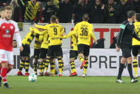 Dortmund's Japanese midfielder Shinji Kagawa (hidden) is congratulated by teammates after scoring during the German first division Bundesliga football match between Mainz 05 and Borussia Dortmund on December 12, 2017 in Mainz.. / AFP PHOTO / Daniel ROLAND / RESTRICTIONS: DURING MATCH TIME: DFL RULES TO LIMIT THE ONLINE USAGE TO 15 PICTURES PER MATCH AND FORBID IMAGE SEQUENCES TO SIMULATE VIDEO. == RESTRICTED TO EDITORIAL USE == FOR FURTHER QUERIES PLEASE CONTACT DFL DIRECTLY AT + 49 69 650050.