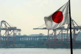The Japanese national flag flies in front of the container pier in Tokyo port on January 24, 2013. Japan said it logged a record trade deficit in 2012, Japan's exports totalled 63.7 trillion yen against imports of 70.7 trillion yen, as exports to debt-hit Europe plunged and a bitter diplomatic spat with its biggest trade partner China weighed on demand. AFP PHOTO / TOSHIFUMI KITAMURA / AFP PHOTO / TOSHIFUMI KITAMURA